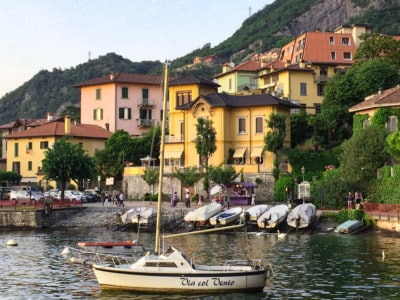 The port of Varenna, a small port with boats on the shoreline, pretty colourful houses and an outcrop with bushes behind.  There is a boat bobbing on the water on the foreground.