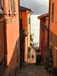 One of Varenna's steep streets leading down to the lake.  You can see orange coloured houses wither side, the lake at the bottom and a person standing at the bottom of the street