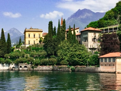 A view of Villa Monastero from the lake.  You can see the yellow main building with other buildings and garden around it.  Mountains are in the background and the lake is in the front.