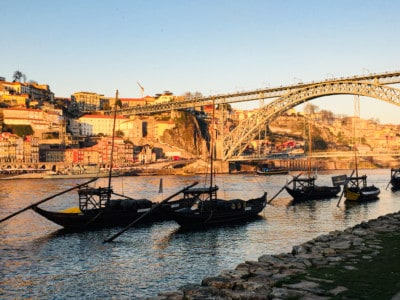 A view of the Douro river at sunset with the bridge over the top and Rebeira in the background.  You can see the rabello boats on the water