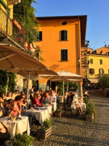 An image of some of the cafes and bars by the lake in Varenna.  You can see tables with parasols and people sitting outside
