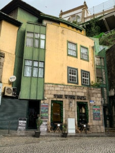 The outside of the Wine Box bar in Porto.  It has a yellow and green exterior.