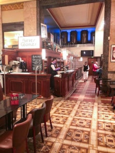 The bar area in Brasserie Georges.  There is a small bar at the side with tables and chairs to sit at.  There are patterned tiles on the floor