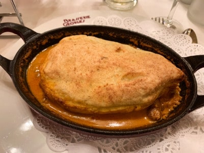 The pike quenelles dish in Brasserie Georges.  This is a pale brown round shape in a brown creamy sauce.  It is served in a small iron dish.
