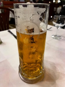 A picture of a glass of Brasserie Georges' own beer.  The glass has their logo on the front.