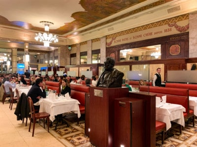 Inside the restaurant.  You can see a few of the tables with diners and a black bust on a pedestal at the front.