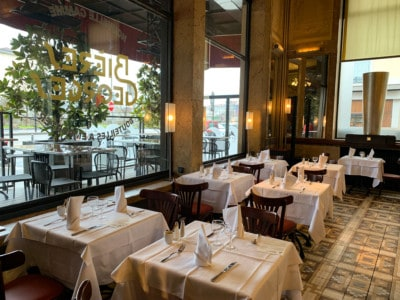 A view inside Brasserie Georges, a place to put on your list when looking for where to eat in Lyon.  You can see 7 tables in the window. They are set for dinner with white tablecloths and napkins etc on the table