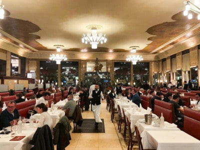 A view inside Brasserie Georges, a place to put on your list when looking for where to eat in Lyon.  You can see the lines of tables with in aisle in the middle.  People are eating at tables and a waiter is in the aisle