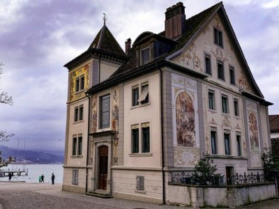 The Unteres Curtihaus house that you can see on a day trip from Zurich.  The outside of the building is decorated with murals.  It has an arched roof.
