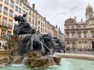 A picture of the amazing statute in Place des Terreaux.  A woman on a chariot in on the top of the pedestal with horses below.  You can also see buildings in the background