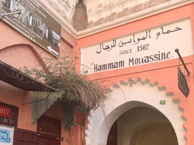 "The outside of the Hammam Mousassine one of the Marrakech hammams you can visit.  This is a public hammam.  The outside is pink with an archway.  The name is above the archway with the note that it has been ""since 1562""."