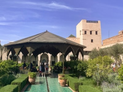 Part of Le Jardin Secret, with a small Moroccan pavilion in the middle, bushes and vegetation and a tower behind.