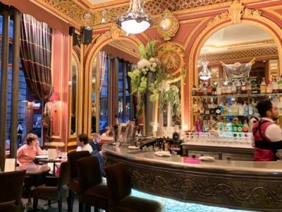 The inside of the Grand Cafe des Negociants that you can visit in 2 days in Lyon.  You can see the bar with large mirrors behind and orange and yellow sculpted walls.
