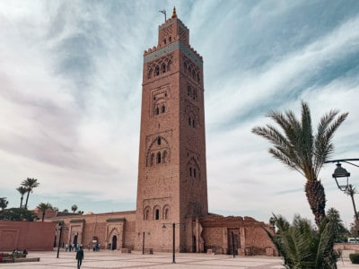 A view of the Koutoubia Mosque, a key sight in Marrakech.  This has a think high tower on the top.  There are palms on the side and a relatively empty square in front.