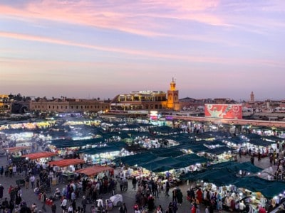 A view of the main square in Marrakech, the Jemaa el-Fnaa.  This is a view at night with the sun setting and taken looking over the square.  You can see the night market and stalls and huge numbers of people
