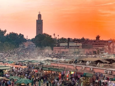 A view of the main square in Marrakech, the Jemaa el-Fnaa.  This is a view at night with the sun setting and taken looking over the square.  You can see the night market and stalls and huge numbers of people.  You can also see the tower of the mosque in the background.