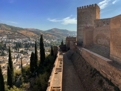 A view out across Granada from the Alcazaba in the Alhambra.  You can see the side of the Alcazaba and the hills in the background with houses below.