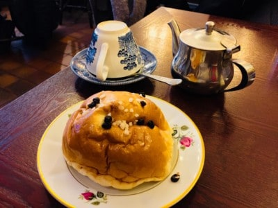 The Bath Bun on a plate with pot of tea and teacup alongside it.