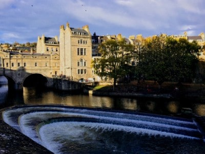 A picture of the river in Bath with the weir and a Georgian building in the background.