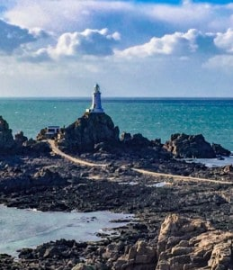 The Corbiere lighthouse in Jersey.  It sits on black rocks and there is a pathway leading up to it.