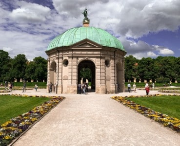 Part of Munich's English garden.  You can see a small pavilion in the middle with a green dome.  There is a pathway leading up to it, with lawns and flower beds on either side.
