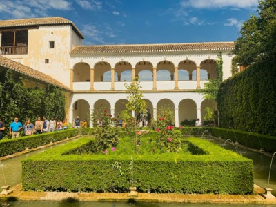 A white building in the Generalife gardens in Spain's Granada.  This has a series of arches on two levels and has neat manicured hedges and bushes in  front of it.