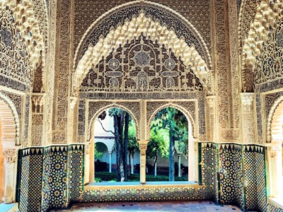 Inside of part of the Nasrid Palace in Granada's Alhambra.  You can see an ornate and colourful archway in Moorish design.