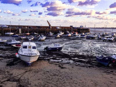 Part of the harbour in Gorey in Jersey.  The tide is out.  You can see some boats in the harbour.
