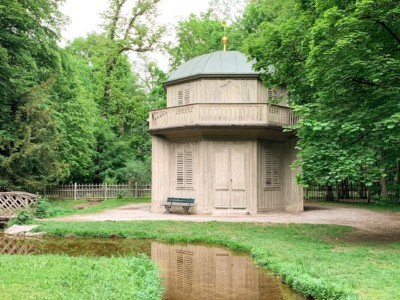 A small pavilion with a balcony in the grounds of Nymphenberg Palace in Munich.  It has a green dome and surrounded by trees.  There is a small stream at the foot of it.