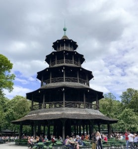 The temple in the Chinese Garden in Munich's English Garden.  It is a tower with four different levels.  There are tables in front of this, with people sitting at these.