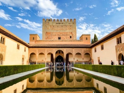 Outside of part of the Nasrid Palace in Spain's Alhambra.  You can see the palace at the far end, a channel of water in the middle leading up to this and neat hedges either side.