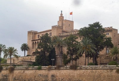 The Alcazar (or Royal Palace of La Almunaina).  There are palm trees in front of this.