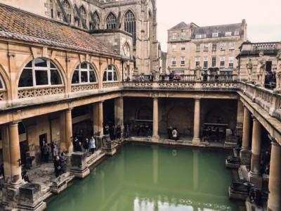 A picture of the Great Bath in Bath's Roman Baths from above.  You can see downwards to the water.  Part of Bath Abbey is in the background.