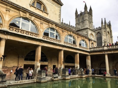 A picture of the Great Bath in Bath's Roman Baths - a destination to put on your ideas for short breaks.  You can see the water in the middle with the building around it.  Bath Abbey can be seen in the background.