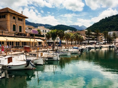 The bay at Port de Soller in Majorca.  You can see the marina with boats moored in it and buildings and trees behind.