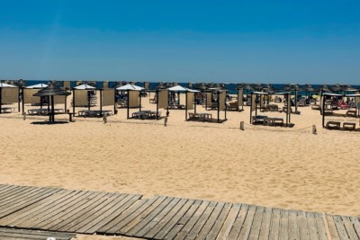A view of the beach in Tavira.  You can see a wide street of sand with a wooden pathway in front.  Thee are rows of beach beds.