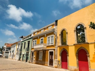 A street in the old town in Portugal's Tavira.  The houses are colourful - yellow and green.