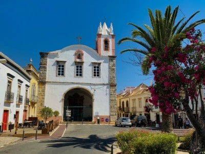 A small pretty square in the Algarve's Tavira. There is a small church here and a palm tree and colourful bush in the foreground.