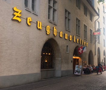 The outside of the Zeughauskeller restaurant.  It has bright yellow signage and a Swiss flag flying outside.