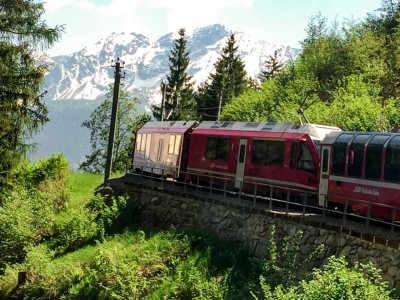 The Bernina Express train riding through the alpine scenery.  There are mountains in the background.