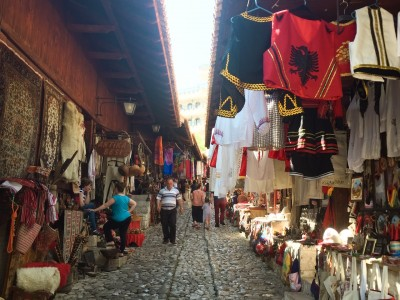 Part of the bazaar - there are fabric wares hanging from the stalls and the overhanging roofs of the stalls.  The street is cobbled and people are wandering through it.