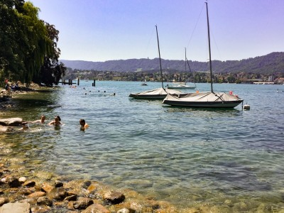 A view of a shallow part of Lake Zurich with people swimming.  There are boats moored in the water.