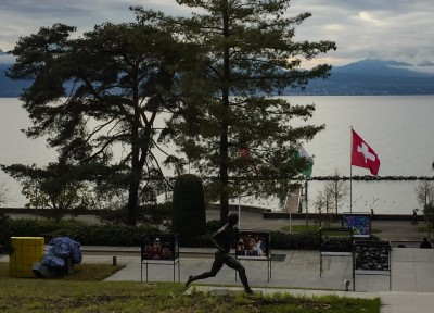 A view of the lake from the Olympic Museum.  There is a statue of a runner on the grass and some balls trees alongside the water.  The Swiss flag is flying.