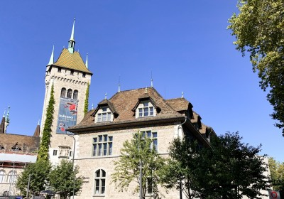 The outside of the Swiss National Museum. It has a tower on the left and there are trees around it.