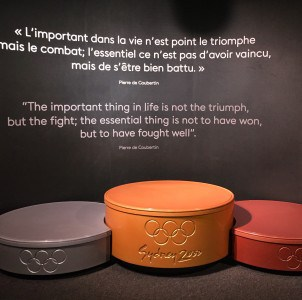 A display of the podium for the medal ceremonies at the Olypmics.  It has a quotation from Pierre De Coubertin above it.