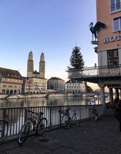 A side view of the Storchen hotel in Zurich.  There is a stork above a balcony on the outside.  Some bikes are tied to a railing on the side of the river.  The Grossmunster church is across on the other side of the river.
