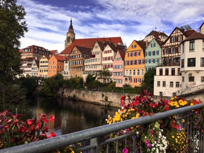 Day trips from Stuttgart: A view of Tubingen from the bridge over the river.  The timbered coloured houses line the river and the cathedral is behind in the background