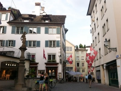 A street in the old town.  There are building with the Swiss flag flying from them and a fountain in the street on the left.