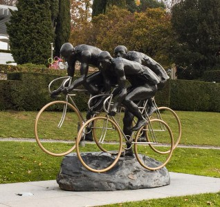 A sculpture on the grass outside the Olympic Museum.  It is a sculpture of 3 cyclists.