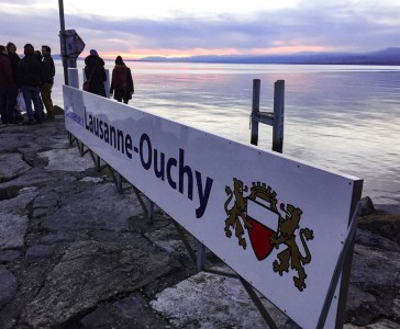 A Lausanne-Ouchy sign on the rocks by the lake in Ouchy